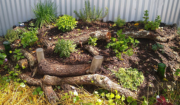 Pictured: an herb garden bed built with small logs
